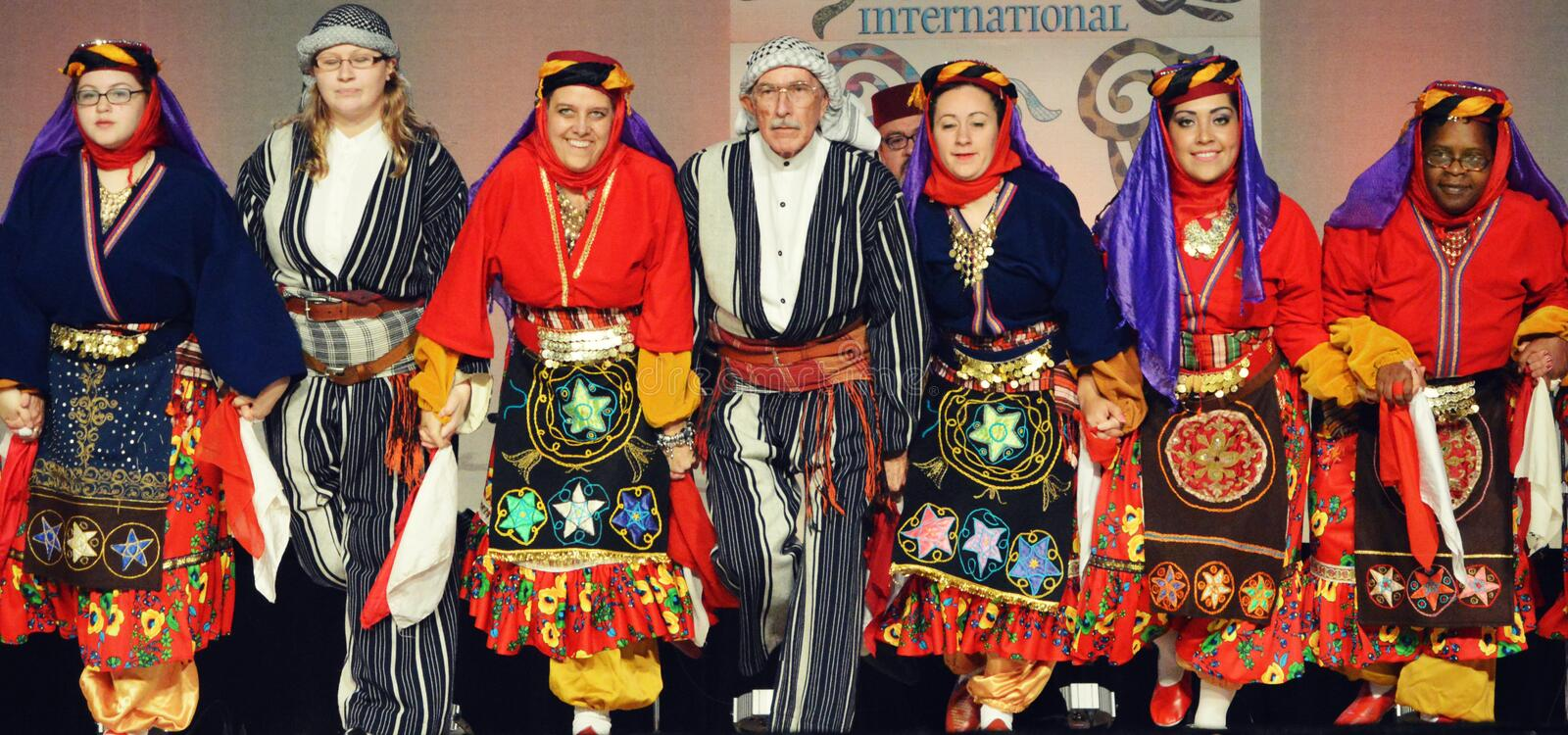 Elderly Man Dancing with Women. An elderly, retired man dancing with a group of women in traditional Middle Eastern dress at the Holiday Folk Fair International stock photography
