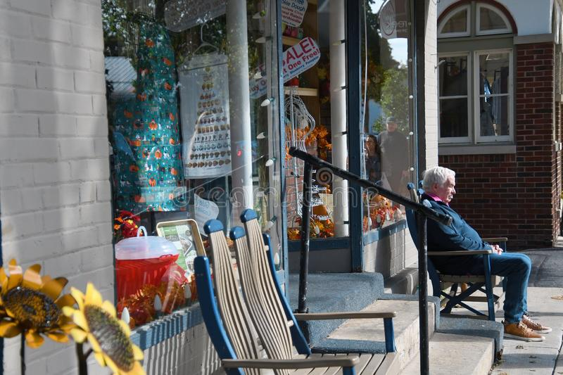 An Elderly Man with Dementia Sits Alone, Lost and Abandoned on a Bench in Front of a Storefront stock image