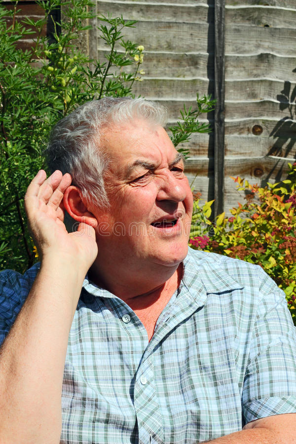 Elderly man difficulty in hearing. An elderly man putting his hand to his ear because he is having trouble to hear royalty free stock image