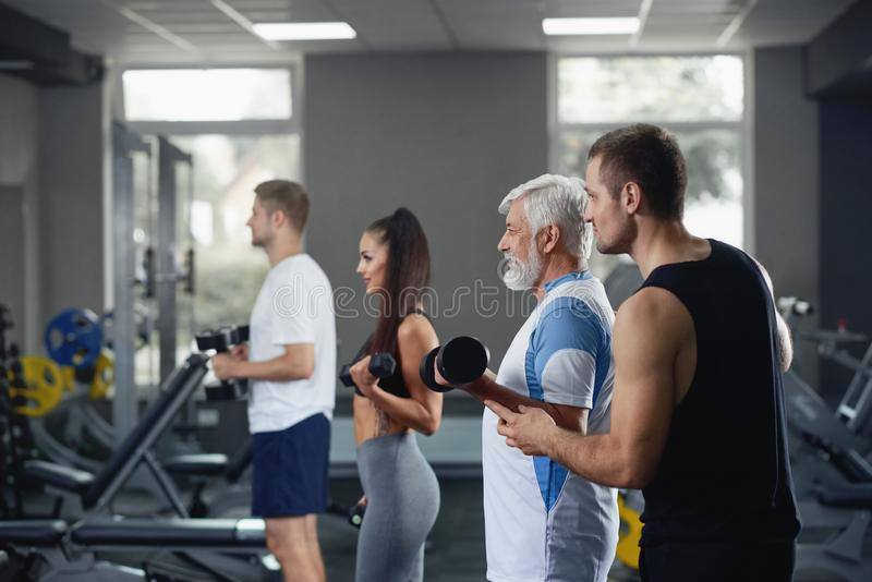 Elderly man doing exercise with group of younger people at gym. royalty free stock photo
