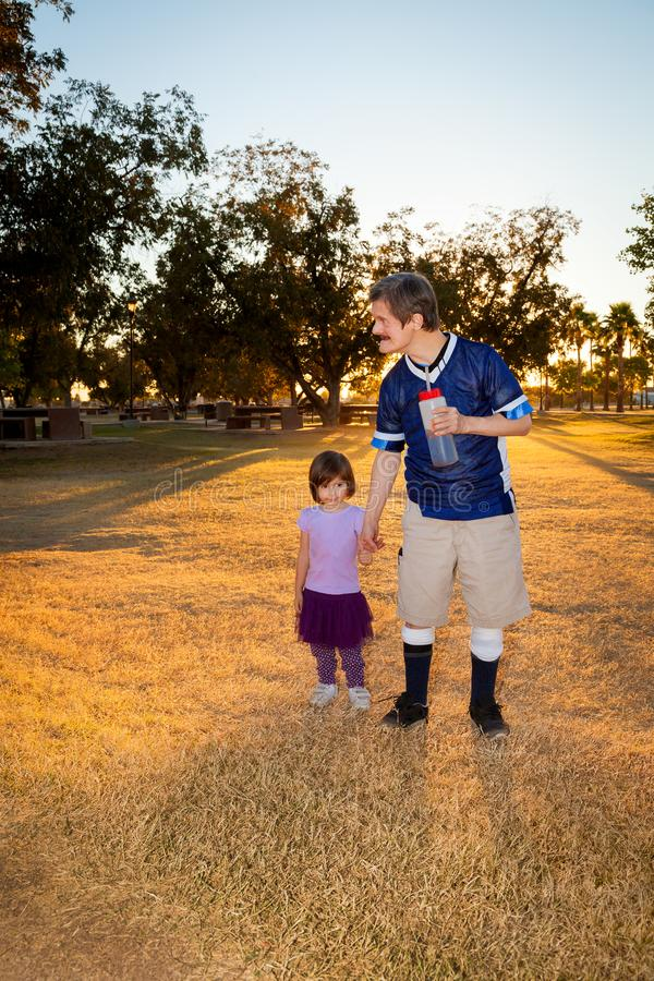 An Elderly Man with Downs Syndrome Holds the Hand of a Young Girl as they Walk Through a Park While the Sun Sets Behind Them. An elderly men with Downs Syndrome stock image