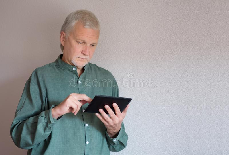 Elderly man dressed in a green shirt stands and holds a tablet using his fingers to browse the Internet. Senior citizens embrace change and make a new stock image