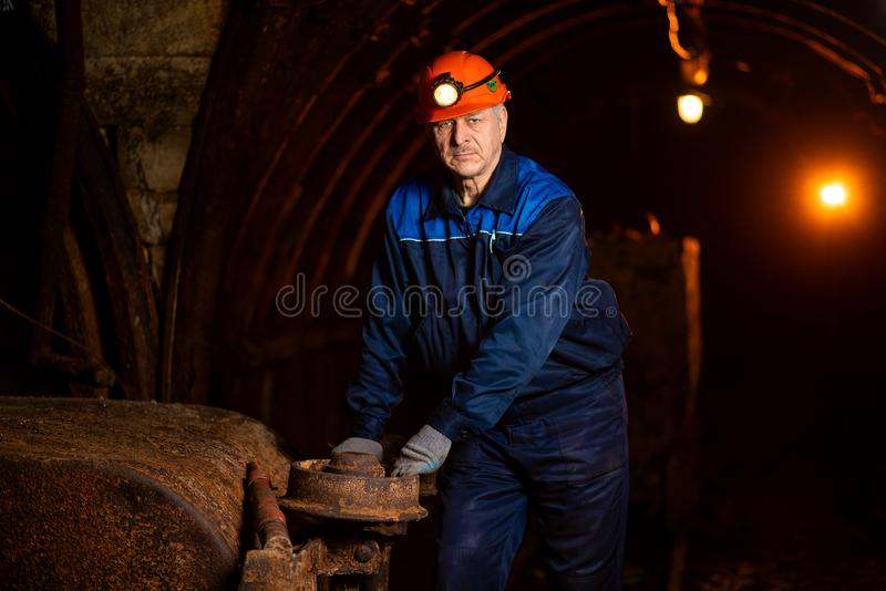 An elderly man dressed in work overalls and a helmet stands near the old inverted vogonetki. Miner stock photo