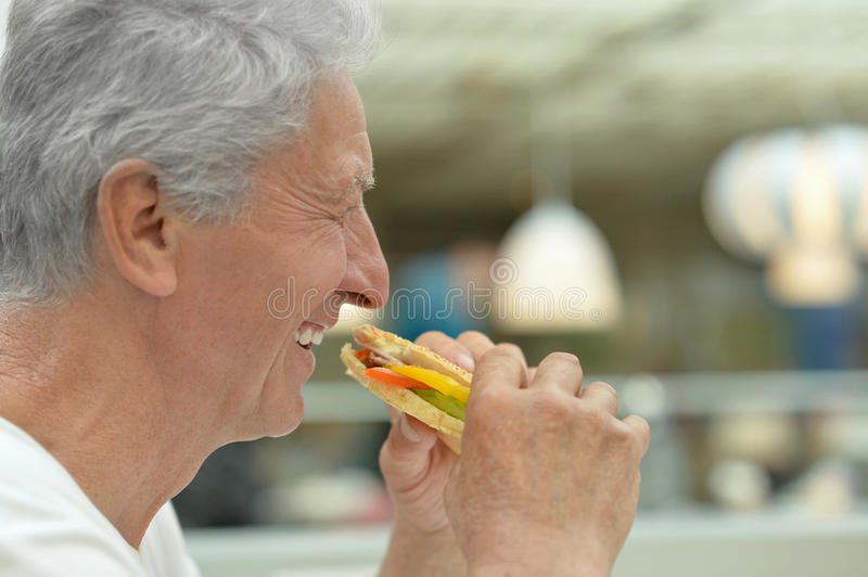 Elderly man eating fast food. Portrait of happy elderly man eating fast food stock photography