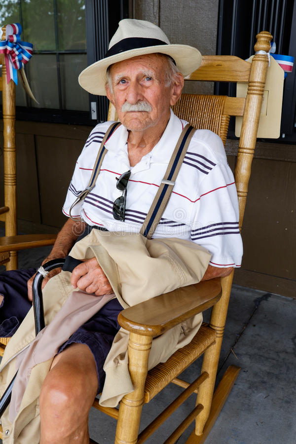 Elderly man. Elderly eighty plus year old man sitting on a rocking chair stock photo