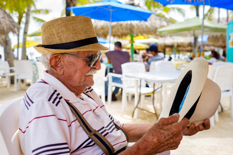 Elderly man. Elderly eighty plus year old man wearing a hat in a outdoor restaurant setting royalty free stock image