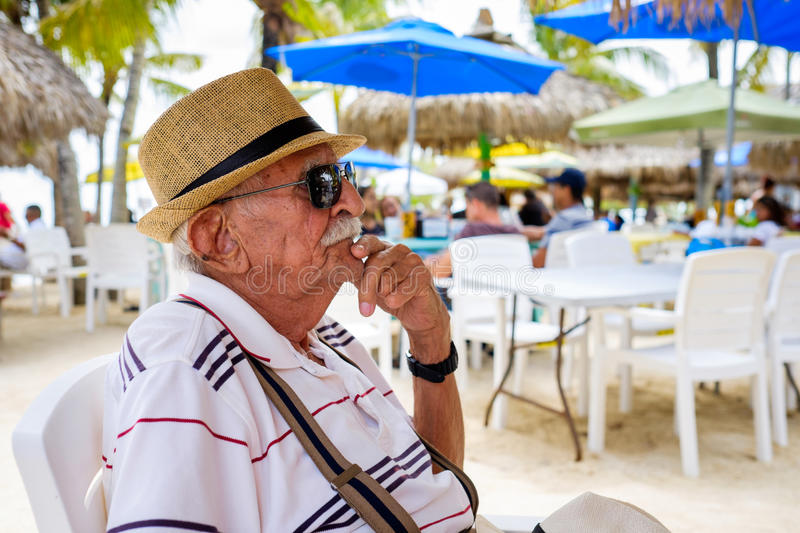 Elderly man. Elderly eighty plus year old man wearing a hat in a outdoor restaurant setting stock image