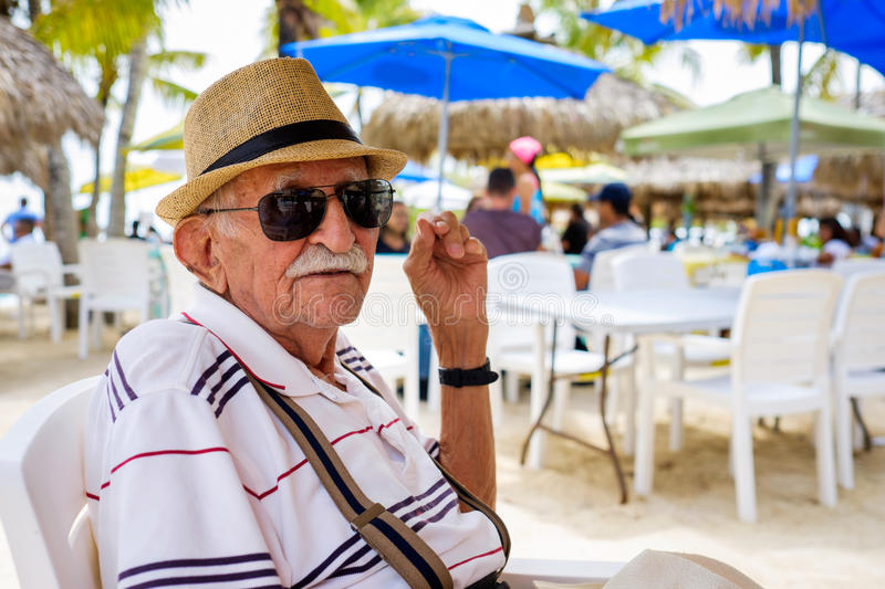 Elderly man. Elderly eighty plus year old man wearing a hat in a outdoor restaurant setting royalty free stock photo