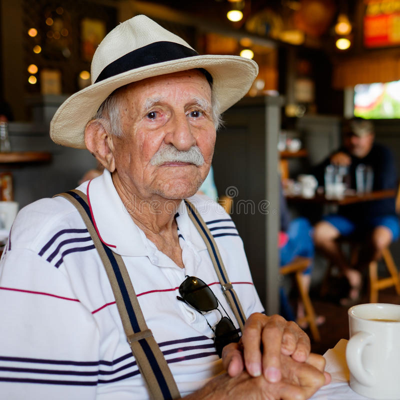 Elderly man. Elderly eighty plus year old man wearing a hat in a restaurant setting royalty free stock photo