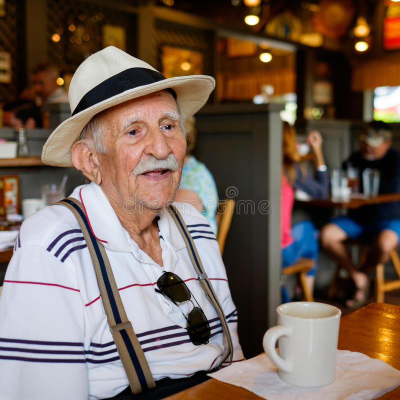 Elderly man. Elderly eighty plus year old man wearing a hat in a restaurant setting royalty free stock image