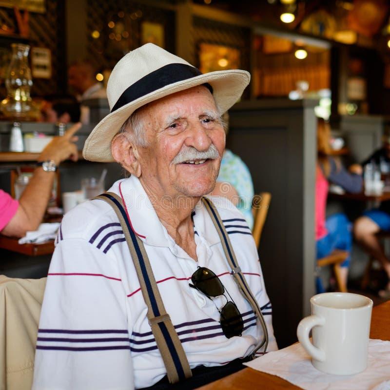 Elderly man. Elderly eighty plus year old man wearing a hat in a restaurant setting stock photos