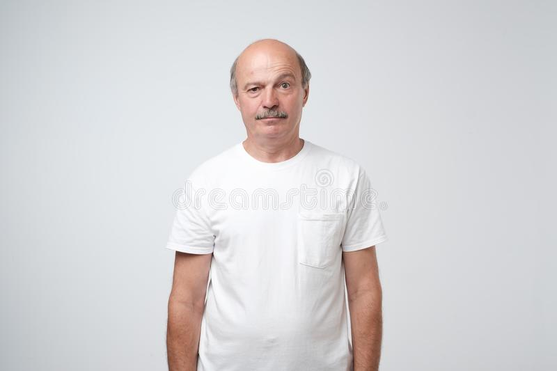 Elderly man emotions, portrait of serious senior caucasian man looking at camera against gray wall royalty free stock images