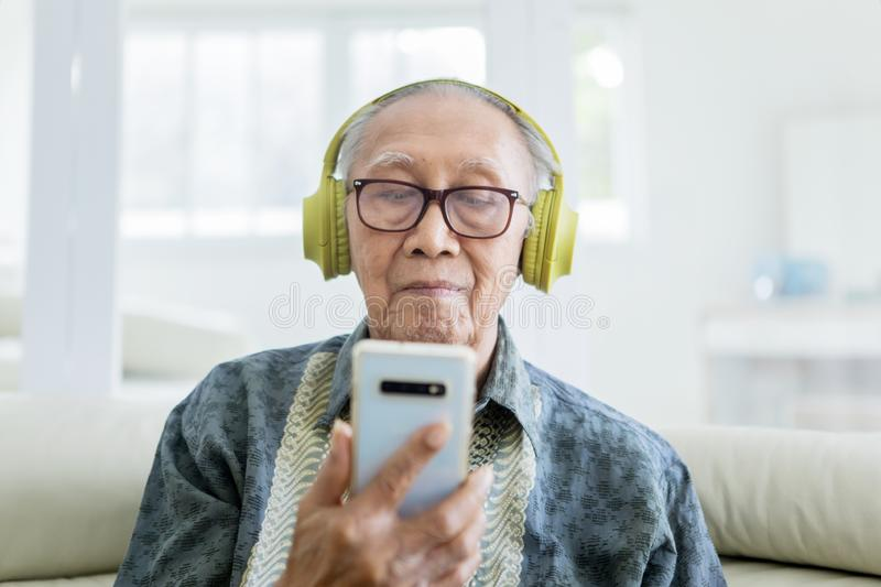 Elderly man enjoying music with a smartphone. Happy elderly man enjoying music with a smartphone and headphones on the sofa at home stock photos