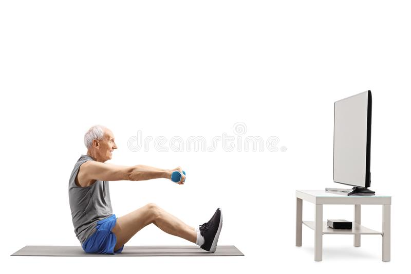 Elderly man exercising with dumbbells in front of a TV. Full length profile shot of an elderly man exercising with dumbbells in front of a TV isolated on white royalty free stock image