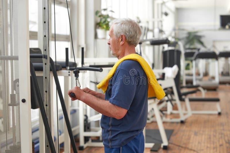 Elderly man exercising at gym. stock photos