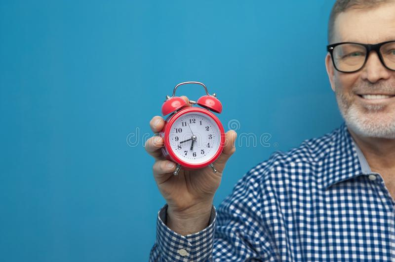 Elderly man in eyeglasses with a little red clock royalty free stock photography