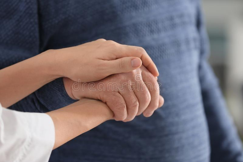Elderly man with female caregiver. Closeup view royalty free stock photo