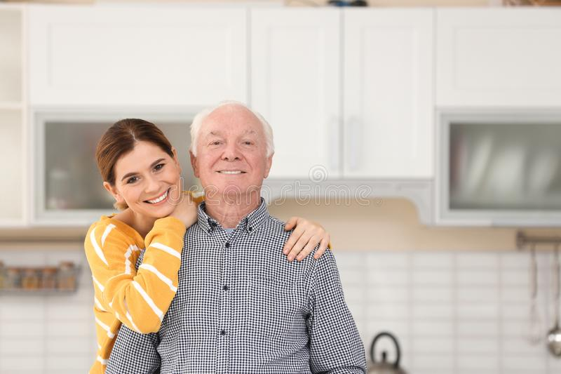 Elderly man with female caregiver in kitchen. royalty free stock images