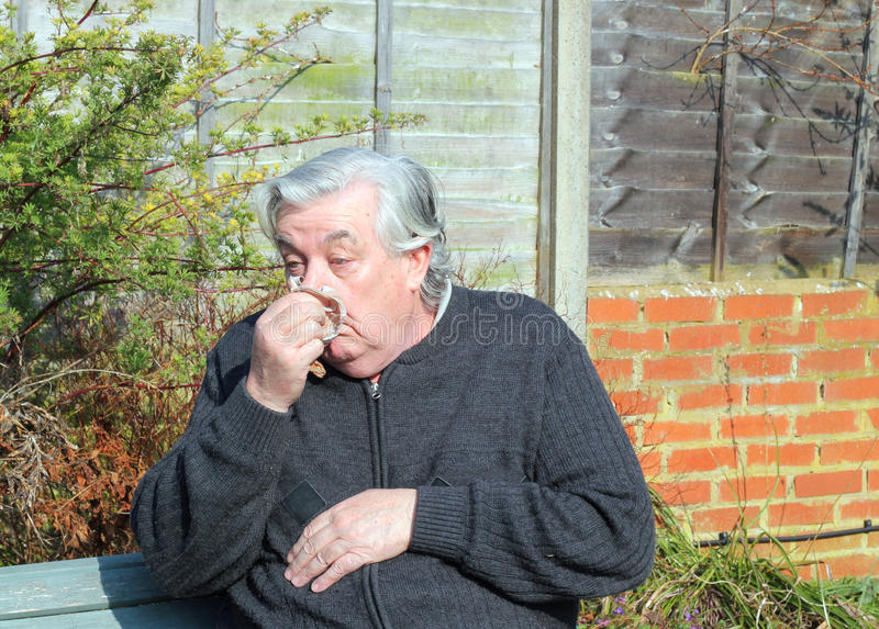 Elderly or old man with flu. An elderly or old man sitting outside feeling ill with running nose as he has flu royalty free stock images