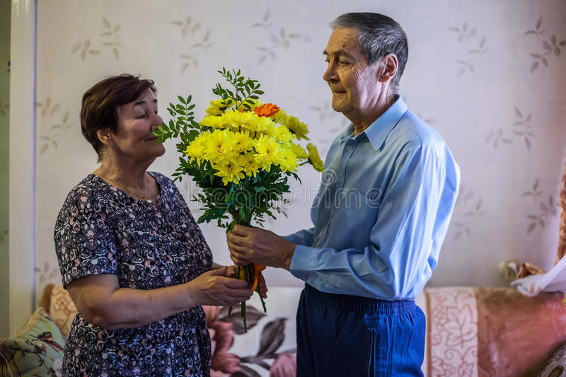 An elderly man gives flowers to his wife stock photo
