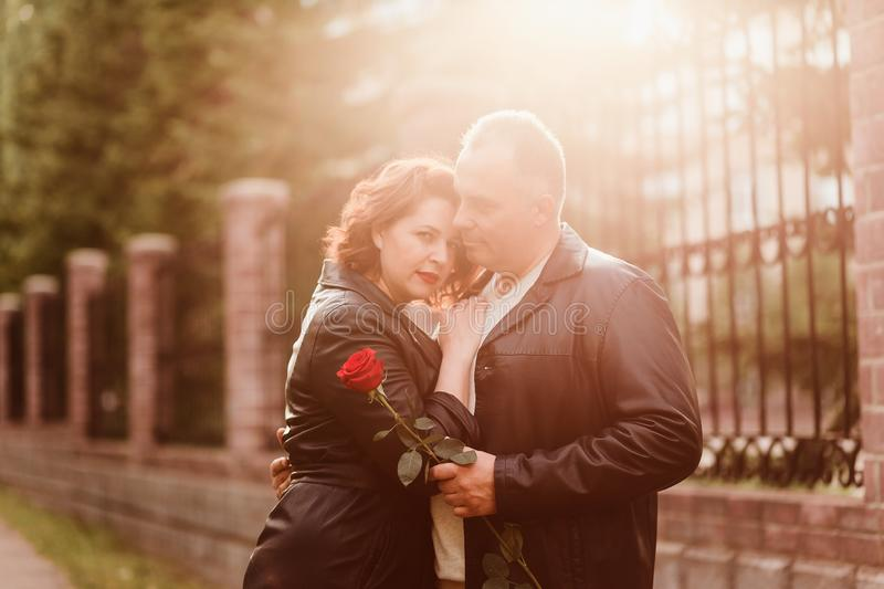An elderly man gives a red rose to a woman. The woman with red lips rested her head on the man`s shoulder. Happy married couple stock photos