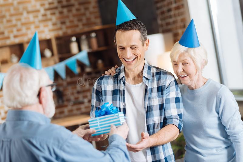 Elderly man giving a birthday gift to his adult son. Token of attention. Pleasant elderly men giving a birthday present to his adult son while the mother hugging stock photo