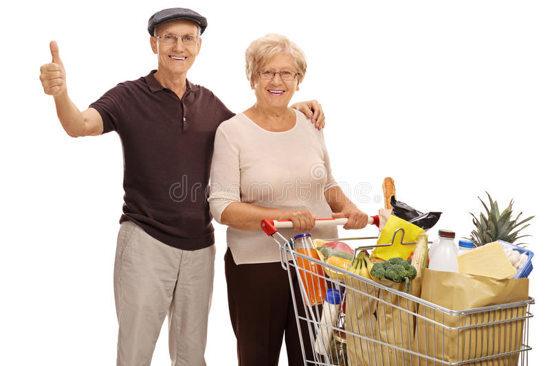 Elderly man giving thumb up and elderly woman with shopping cart. Elderly men giving a thumb up and an elderly women with a shopping cart full of groceries stock photo