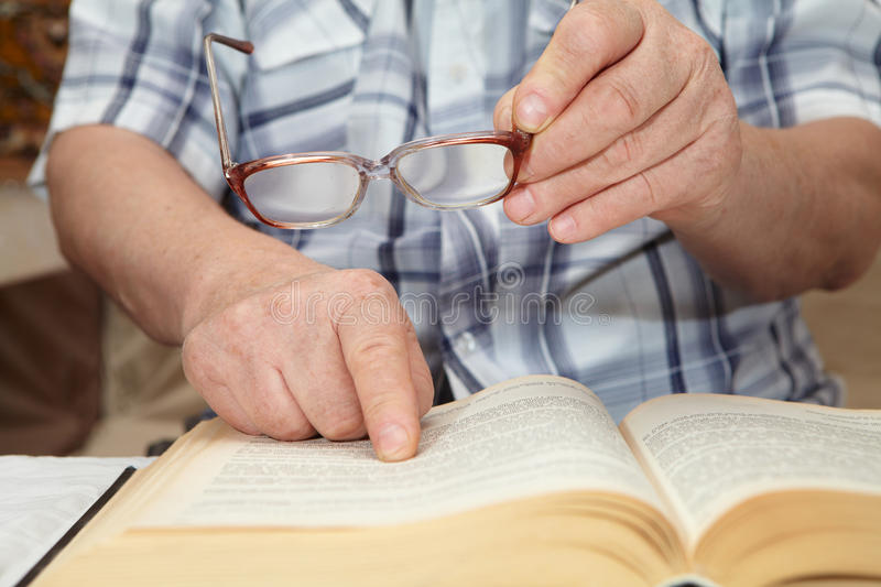 An elderly man with glasses reading a book. Senior people health care stock photography