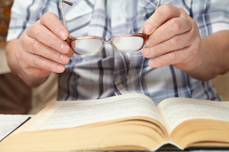 An elderly man with glasses reading a book. Senior people health care stock image