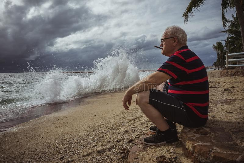 Elderly man in glasses and a striped t-shirt sitting on the beach and looking at the storm smokes a cigar. A wise man in stock image