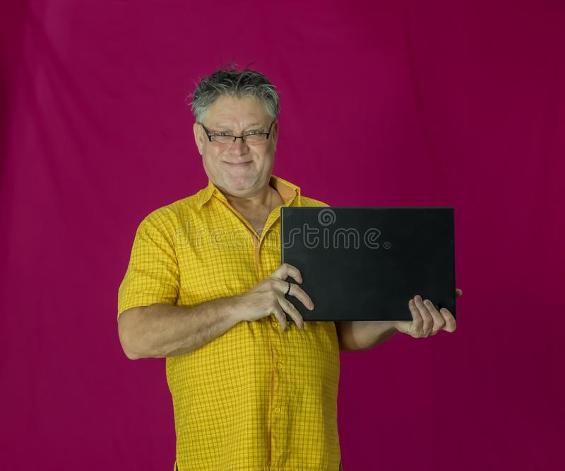 An elderly man with gray hair holds a laptop in his hands. royalty free stock photo