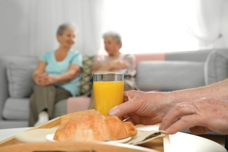 Elderly man having breakfast at nursing home, closeup. Assisting senior people stock photos