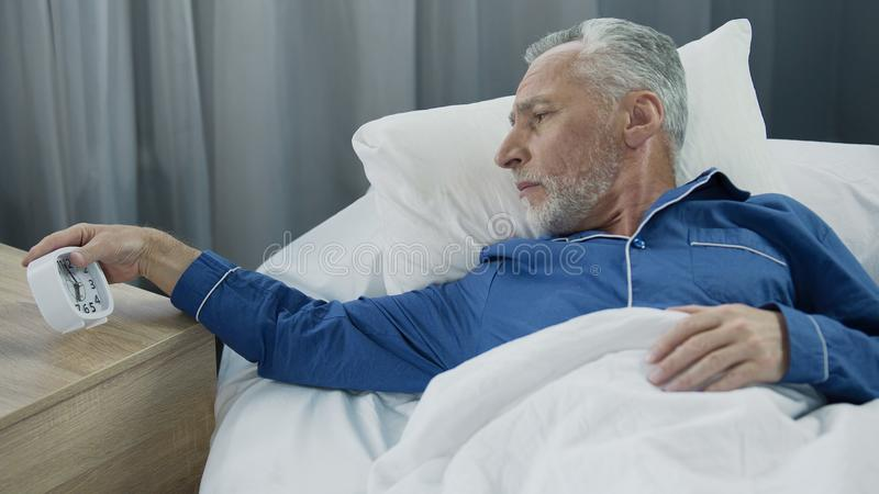 Elderly man hearing alarm clock, reluctant to wake up, lack of sleep and energy royalty free stock photography