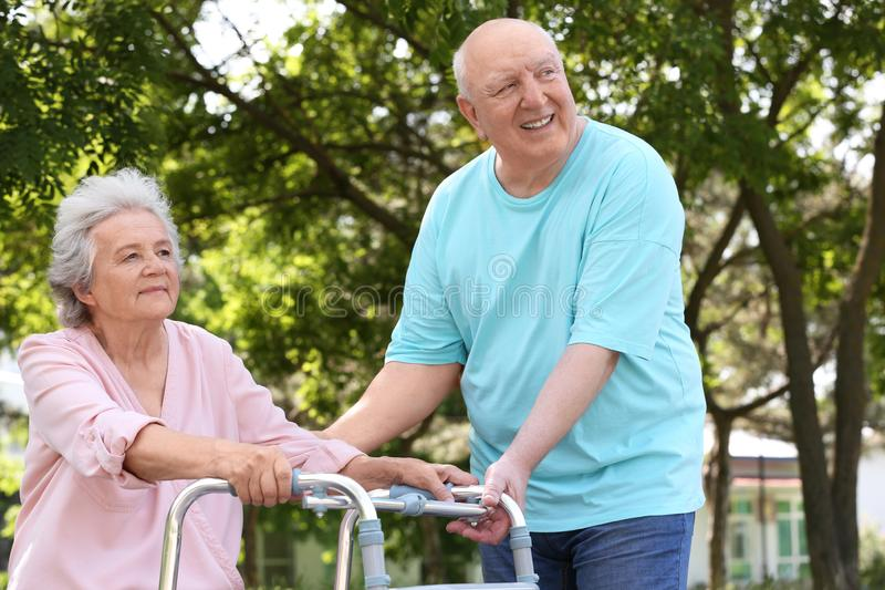 Elderly man  his wife with walking frame outdoors stock photography