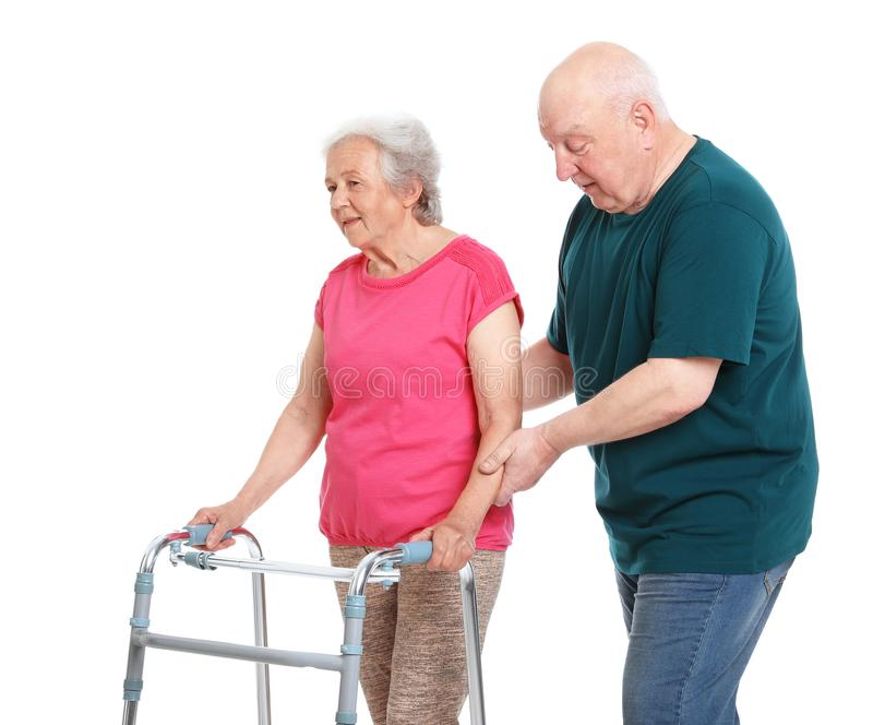 Elderly man helping his wife with walking  on white background royalty free stock photo