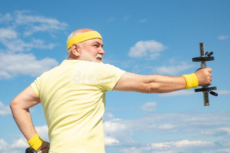 Elderly man after her workout. Senior sportman exercising with lifting dumbbell on blue sky background. Isolated, copy stock images