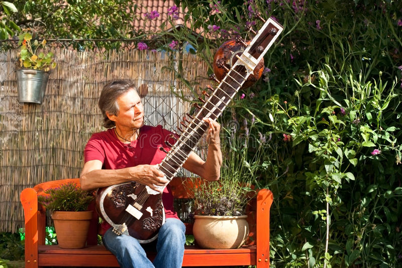 Elderly man in his garden is playing a sitar. Relaxed man sitting in his garden and playing sitar royalty free stock photography