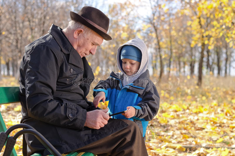 Elderly man with his grandson in the park royalty free stock images