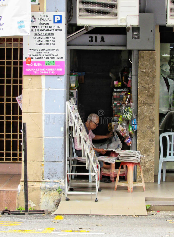 An Elderly Man And His Little Store. A bespectacled elderly man and his little shop at the foot of a flight of stairs, tucked in between 2 larger shops. Items on stock photo