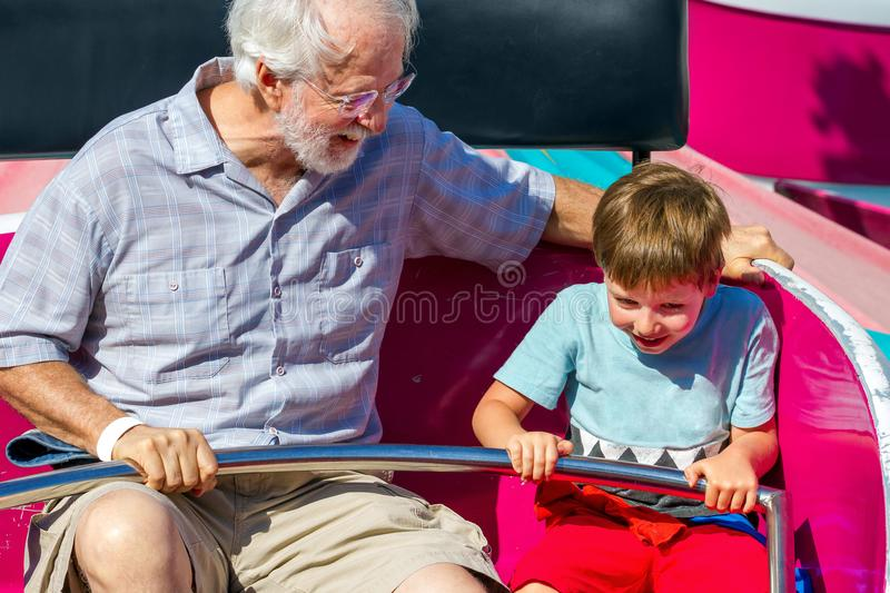 An Elderly Man and His Young Grandson Ride on a Spinning Carnival Ride the Man is Looking at the Little Boy stock photography