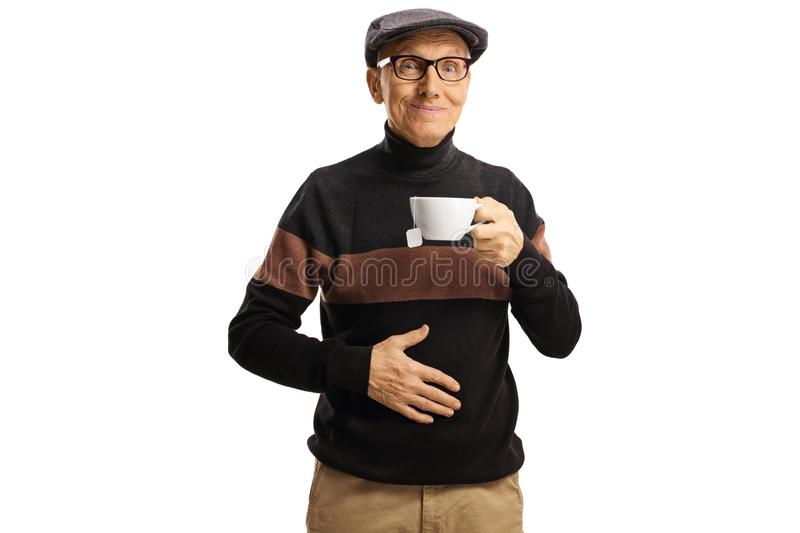 Elderly man holding a cup of tea and his hand on his abdomen stock photo