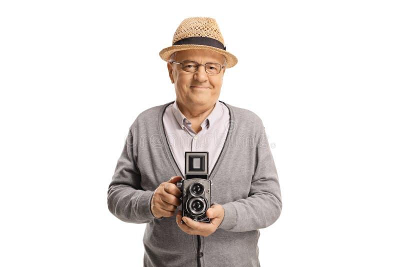 Elderly man holding an old-fashined vintage camera. Isolated on white background royalty free stock photos