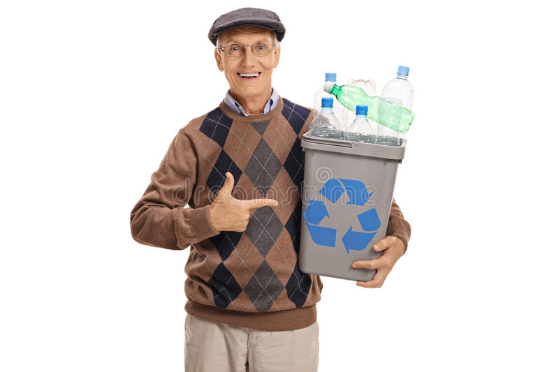 Elderly man holding a recycling bin and pointing stock photo