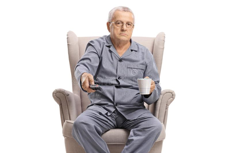 Elderly man holding a remote control and a cup sitting in an armchair royalty free stock photos
