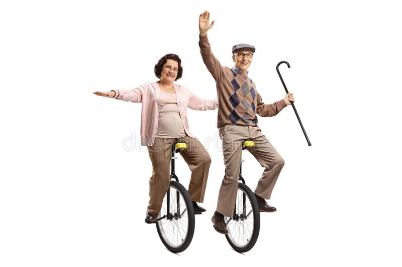 Elderly man holding a walking cane and an elderly woman riding unicycles and smiling royalty free stock photography