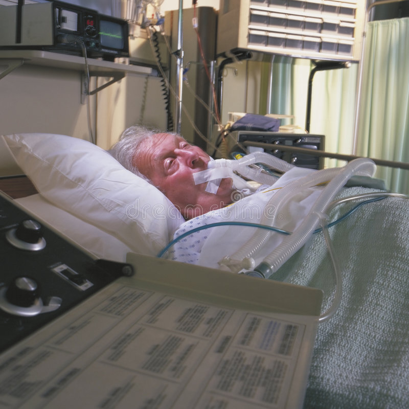 Elderly man in hospital bed stock image