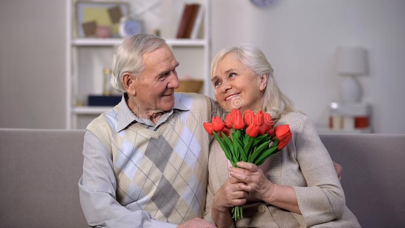 Elderly man hugging happy woman with bunch tulips, present greeting, attention royalty free stock images