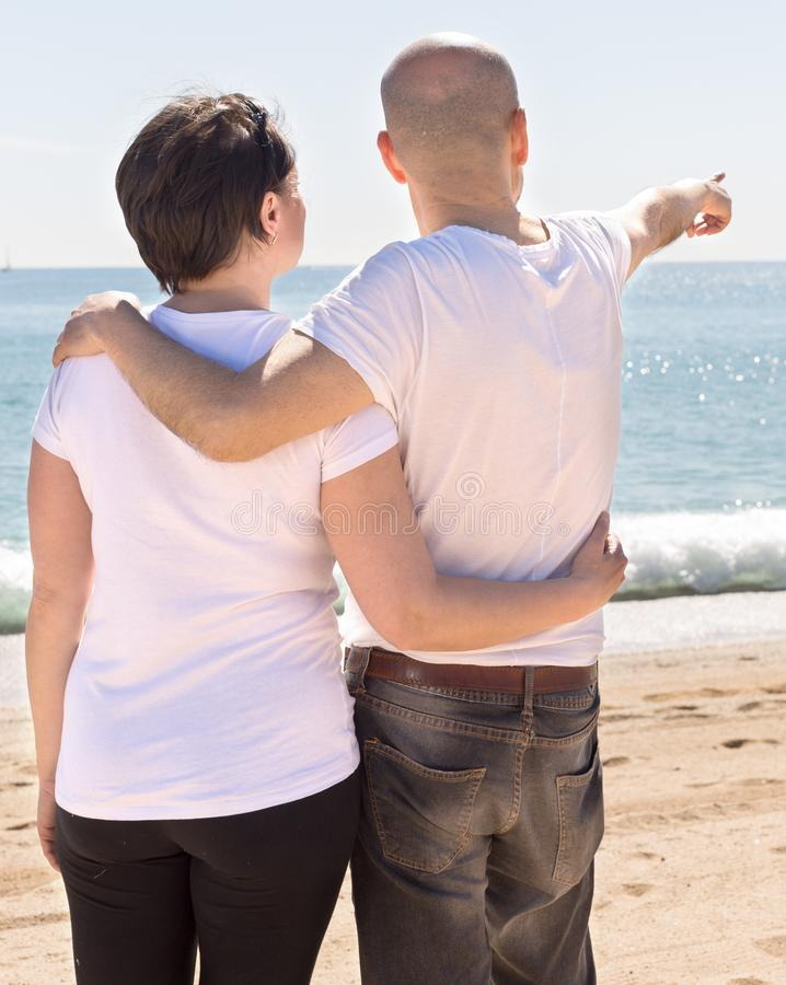 Elderly man hugs a woman on the beach. view from the back. Elderly men hugs female on the beach and indicates into the distance. view from the back stock photography
