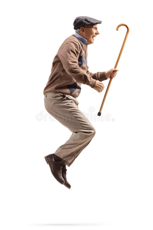Elderly man jumping and holding a walking cane stock images