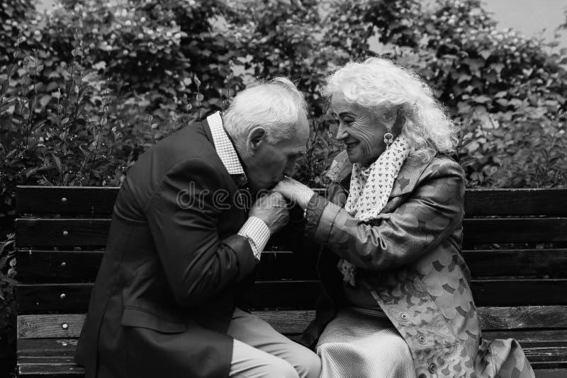 elderly man kisses hands of the elderly woman black and white